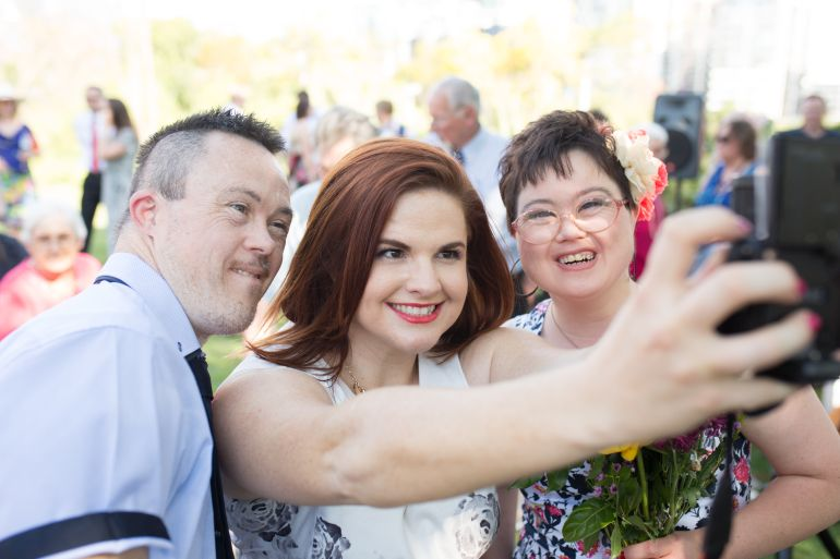Fun celebrant Alana Salm taking a group selfie with a newlywed couple after the ceremony.